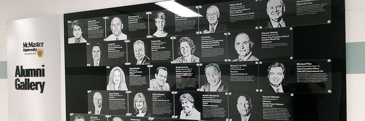 Black & silver display wall with photos of distinguished alumni etched in