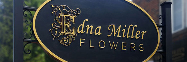 Black carved sign with carved intricate gold letters, Edna Miller Flowers, Hung between 2 posts