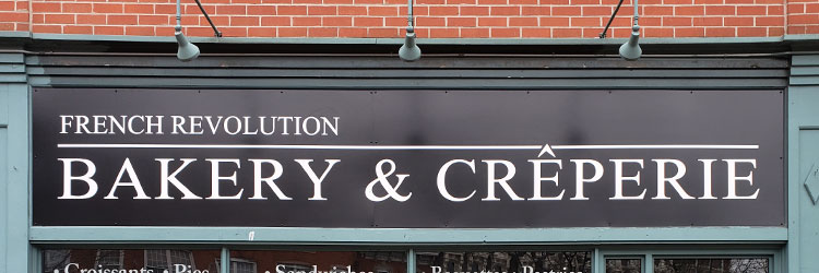 Black storefront sign with white letters applied